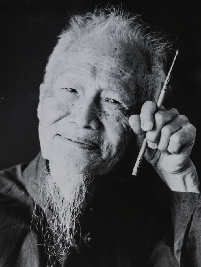 Black and white photo. An elderly man is smiling. His hand, which is held to his face grips a paintbrush between his index and forefinger
