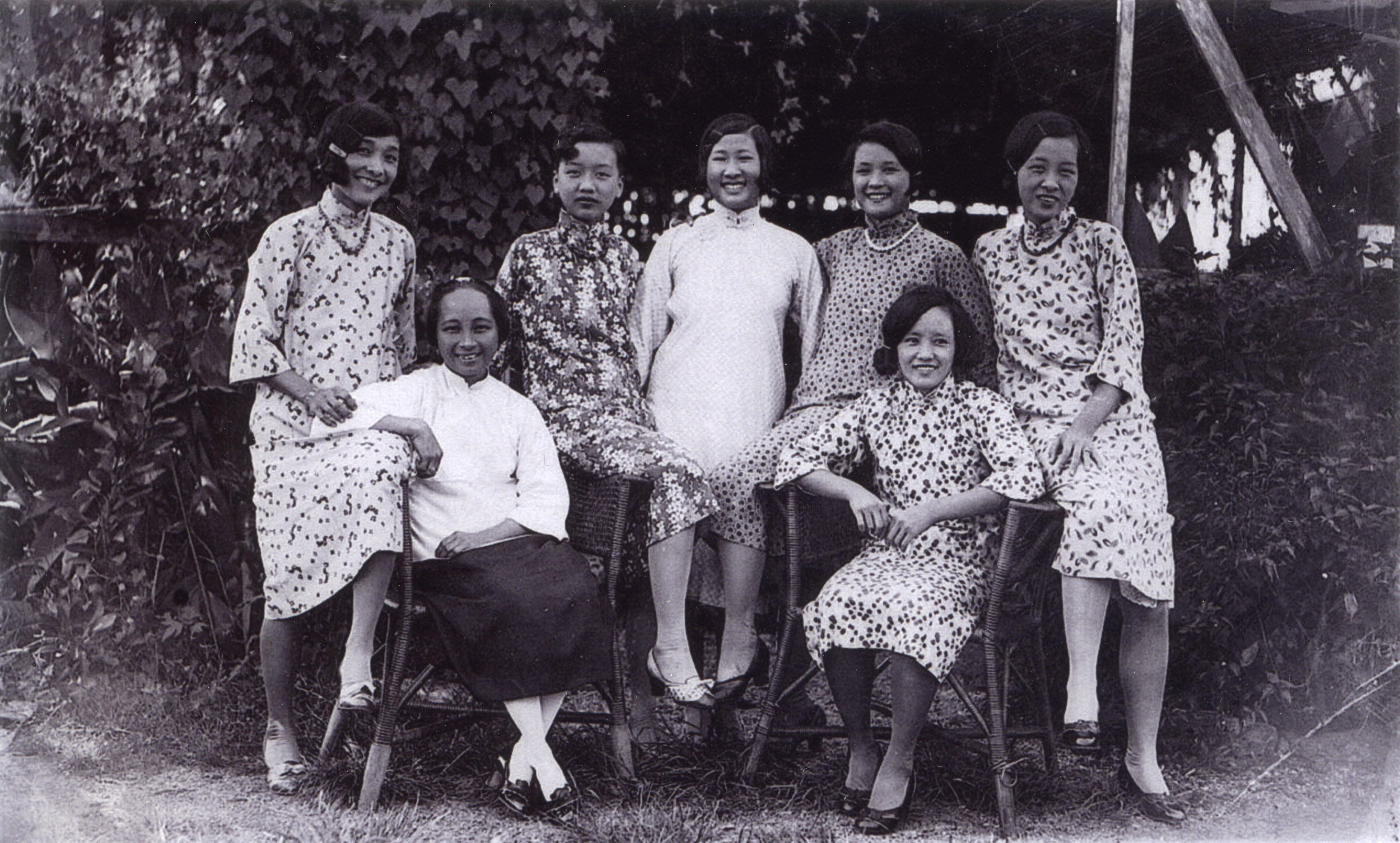 Black and white photo. Seven women standing together and smiling.