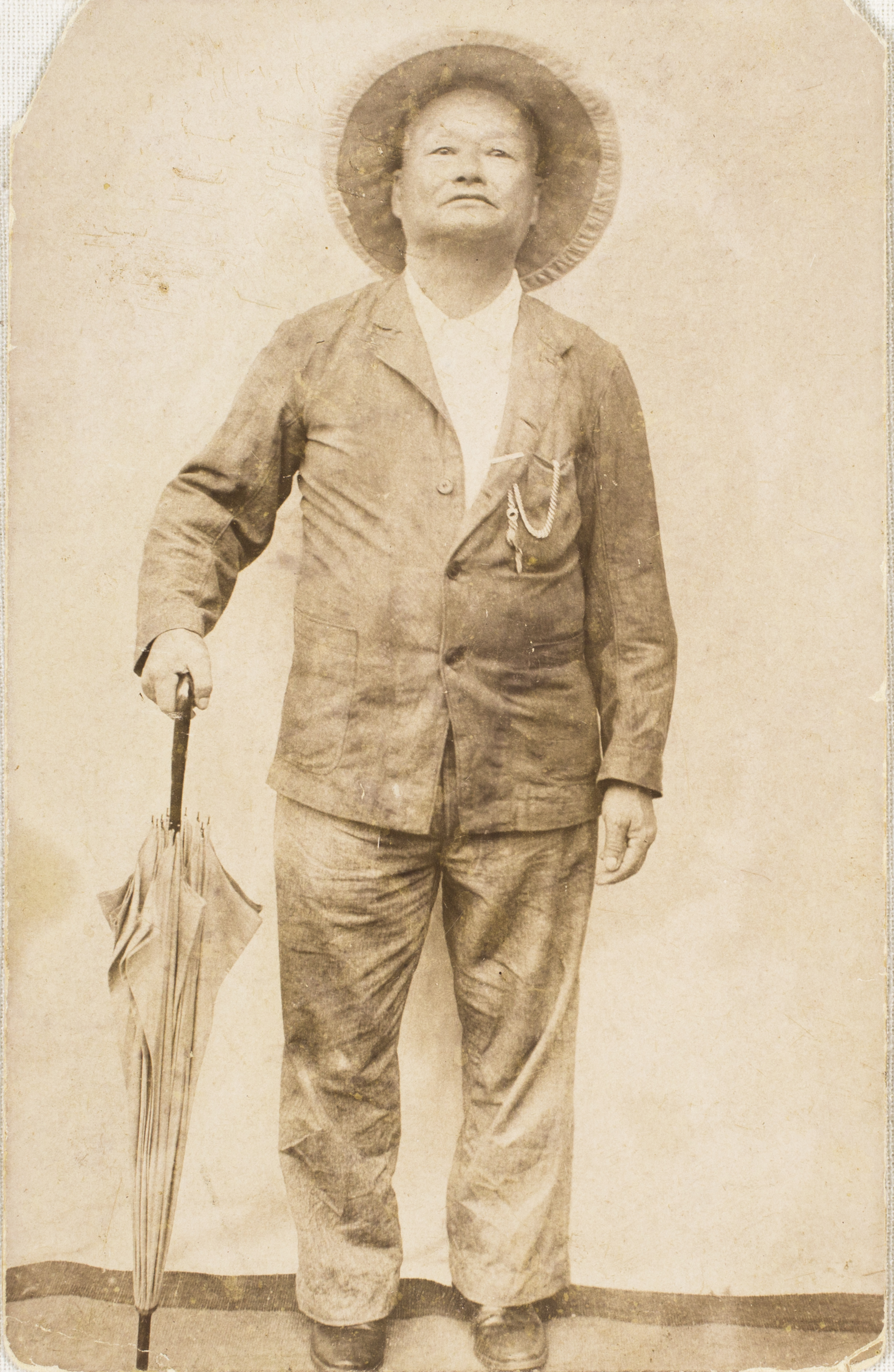 Man standing upright. He holds onto the handle of a folded umbrella by his side