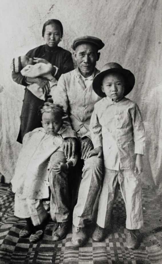 Black and white photo. Man and woman with their children. Woman holds baby in her arms.