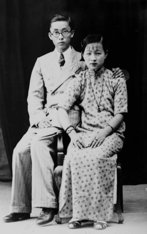 Black and white studio portrait. Man and woman are both seated, the man has this arm around the woman's shoulder