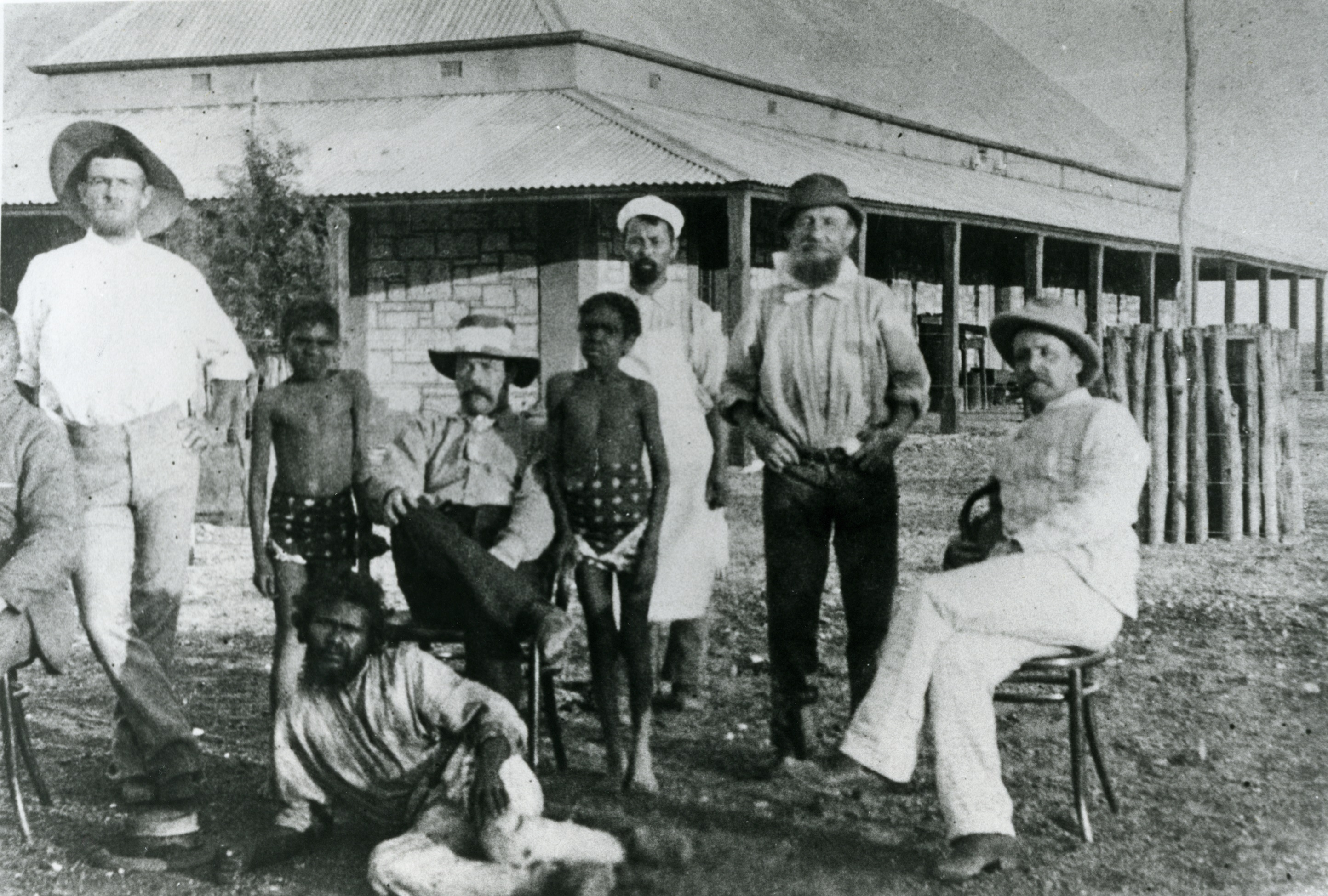 Depicts a group of Aboriginal and non-Aboriginal men and boys in front of a stone building.