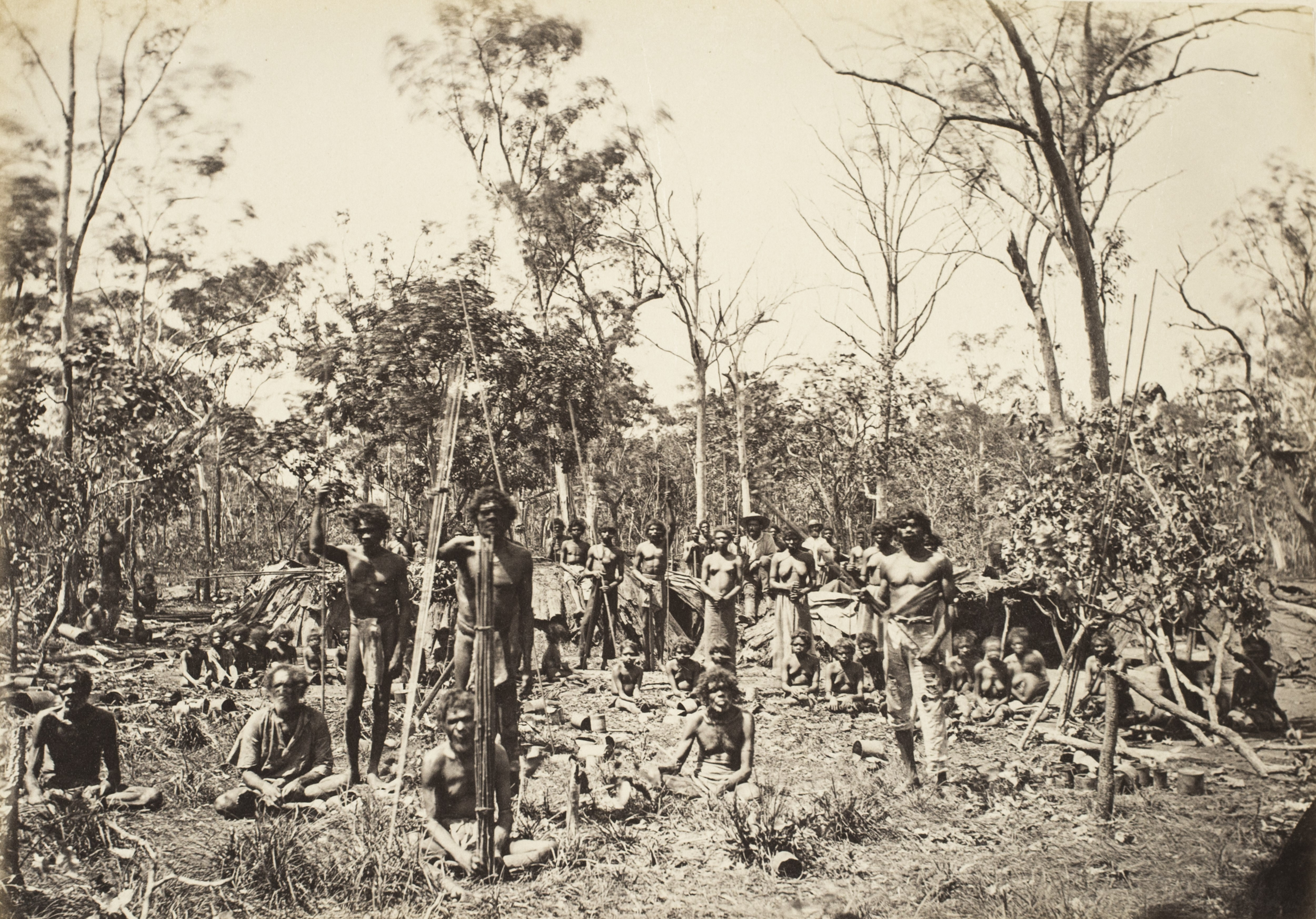 Depicts a group of Aboriginal women, men and children in a camp setting in the bush.