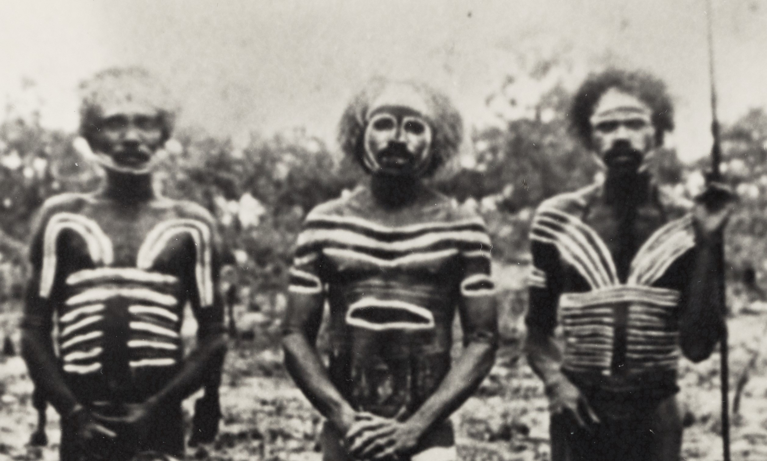 Depicts three Woolnah men painted for ceremony.