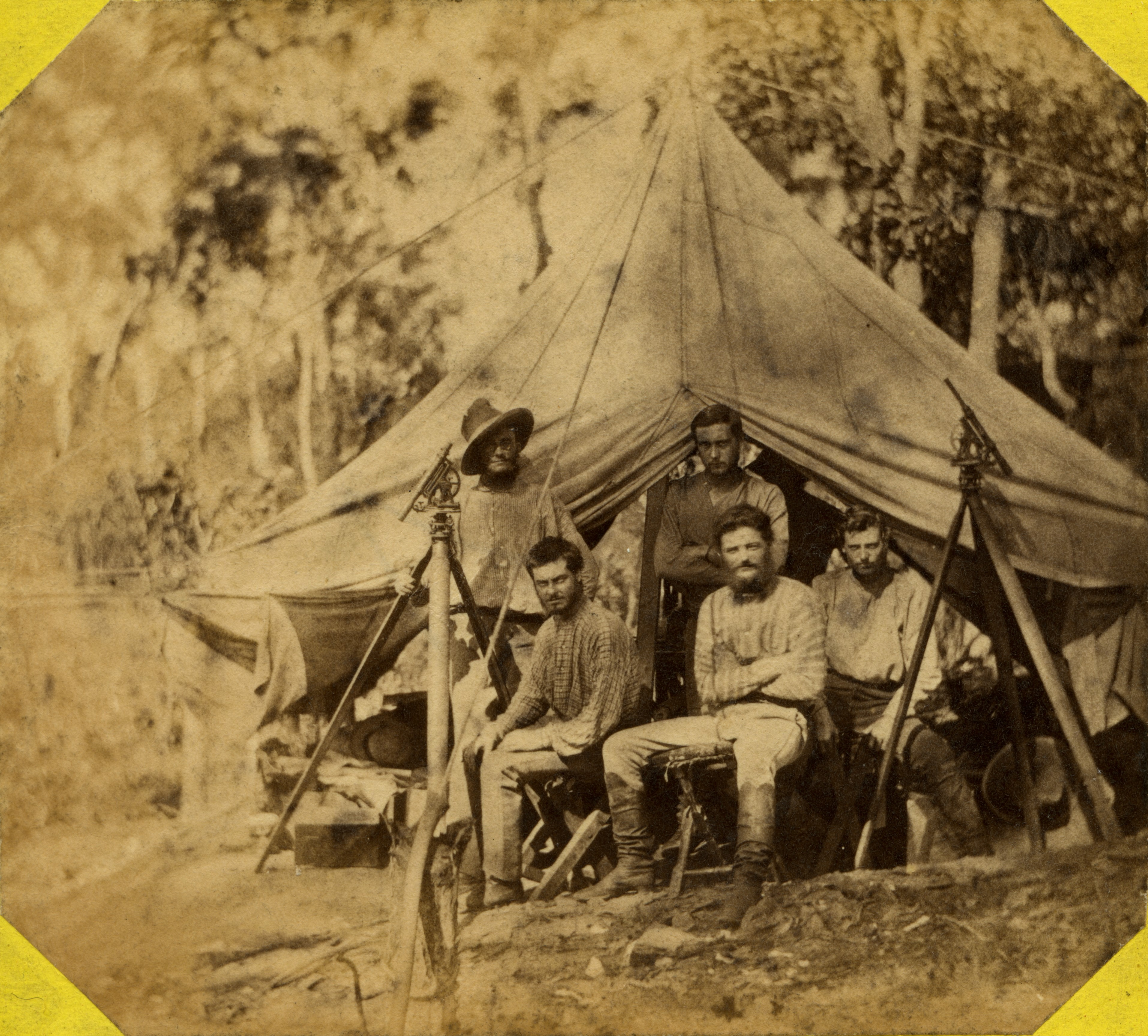Depicts six surveyors at rest in front of an open tent with two theodolites at left and right.
