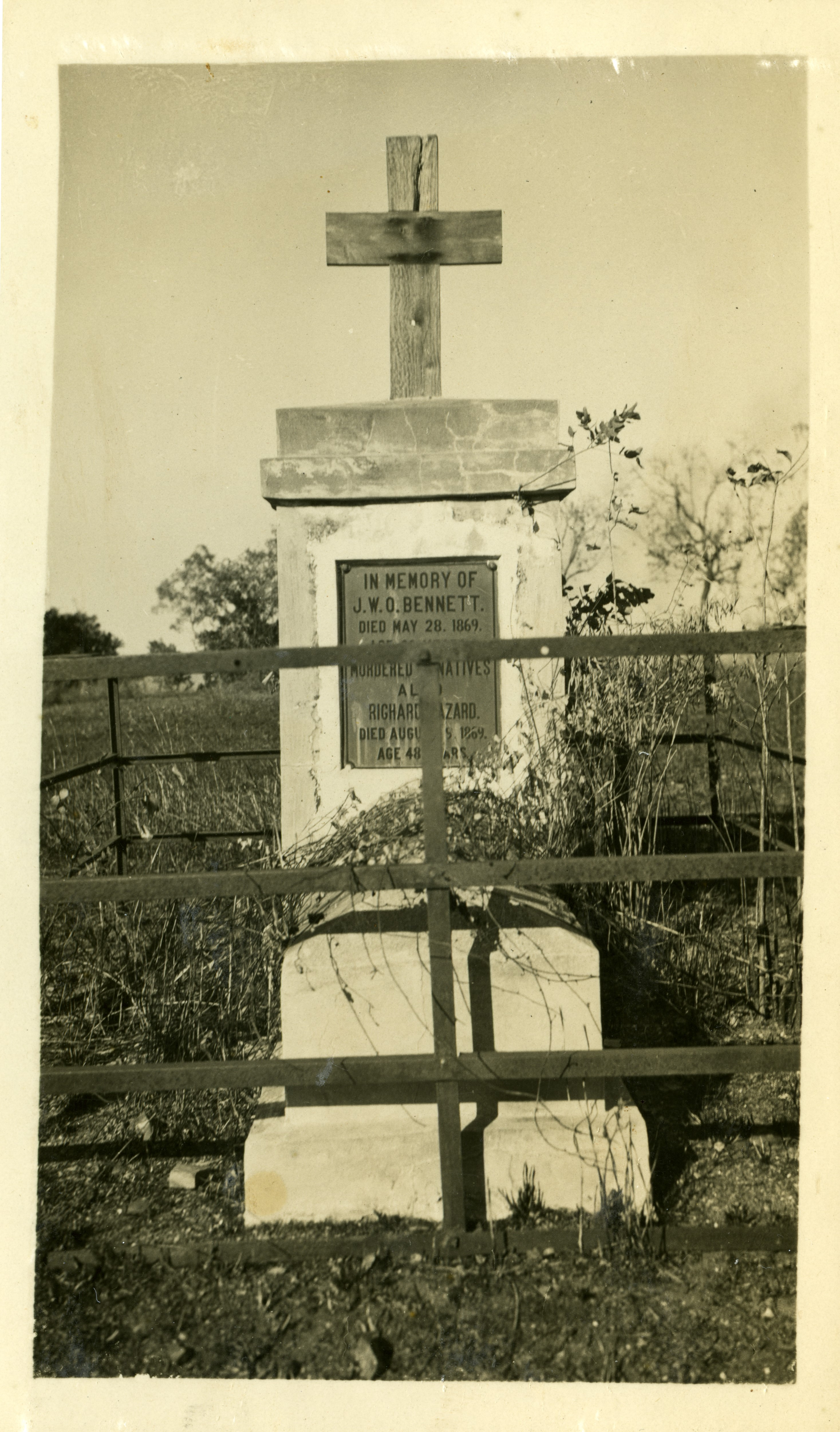 Depicts John Bennett's grave behind a wooden fence. The grave is a high stone pedestal with a wooden cross on top and a bronze memorial plaque at front.