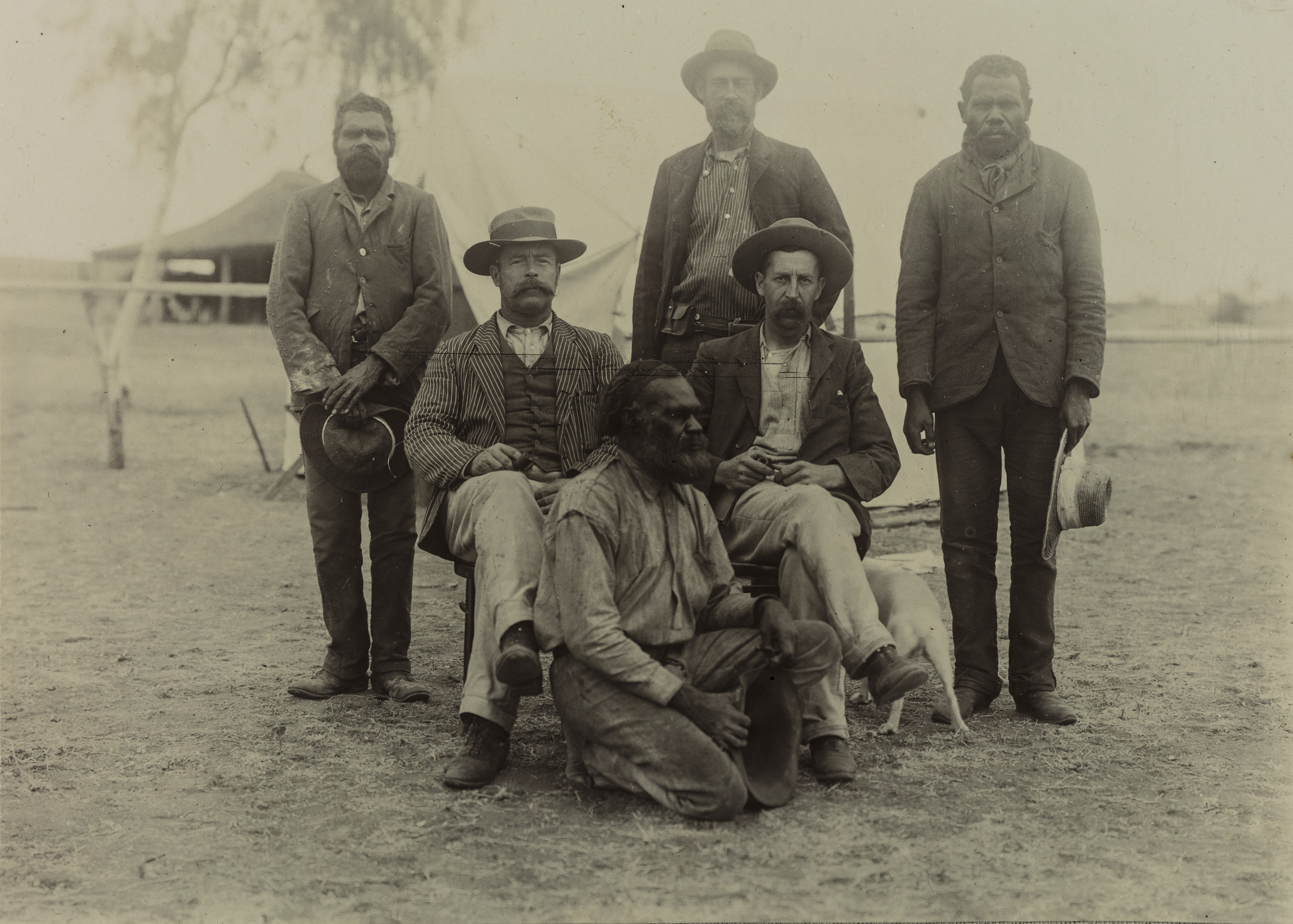 Depicts three Aboriginal men and three non-Aboriginal men posing for the camera in front of their camp.
